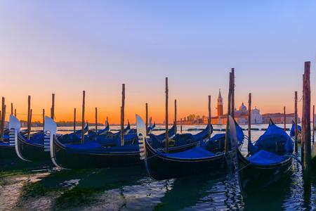 Gondolas moored by Saint Mark square with San Giorgio di Maggiore church in Venice, Italy