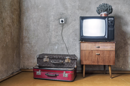 old room. retro tv and two suitcases