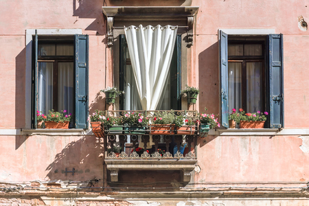 old facade.windows and balcony decorated with flowers