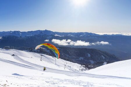 Paragliding on the background of snow-covered white mountains