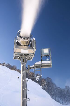 The work of snow cannons on a background of winter mountains