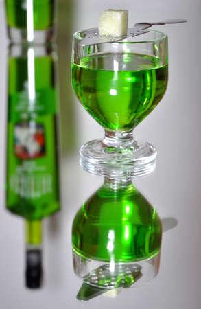 ajenjo: Copa de ajenjo de licor con una cuchara y el az�car en una superficie lisa en contra de una botella