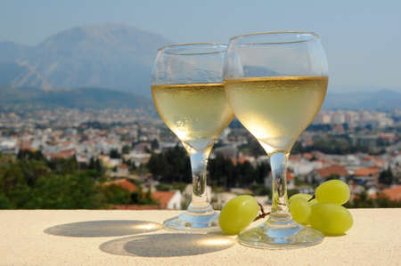 cooled: Two glasses with the cooled white wine and green grapes against mountains