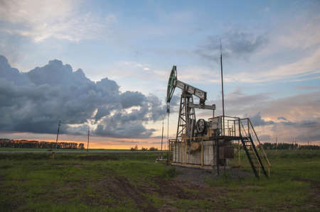 Working pumpjack in field on sunset background