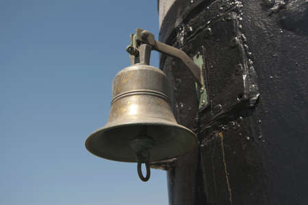 the old ship's bell on the background of blue sky
