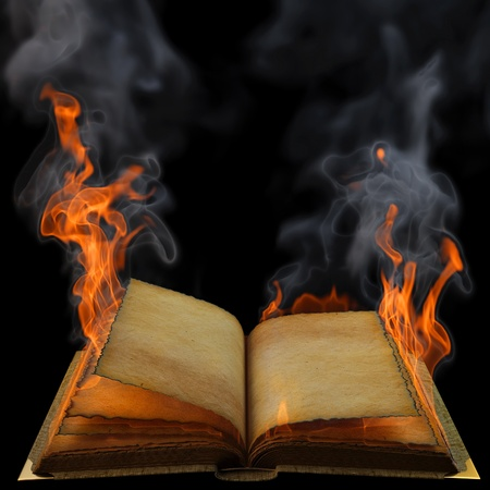 마법의: old empty open book in the flame. isolated on black.