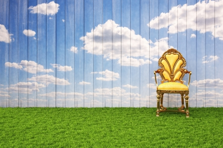 wooden wall with painted sky and floor from the green grass. on the grass stands a luxury chair. photo