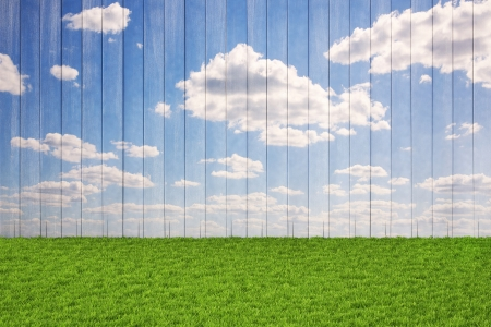 wooden wall with painted sky and floor from the green grass. photo