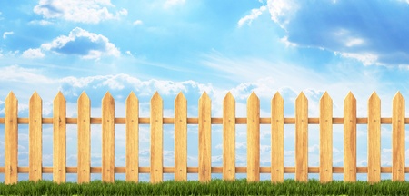 wooden fence with green grass and blue sky photo