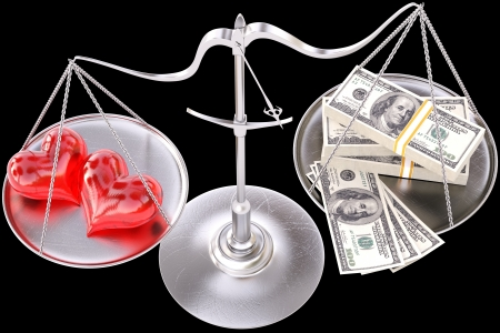 outweigh: two loving hearts outweigh the money. Isolated on black. Stock Photo