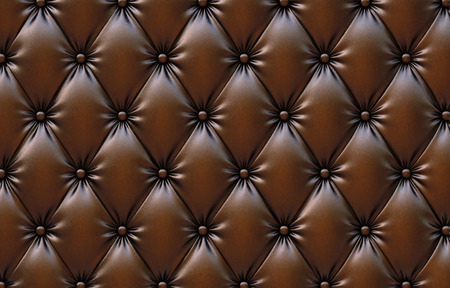 brown leather sofa: luxurious texture of chocolate-colored leather upholstery. Stock Photo