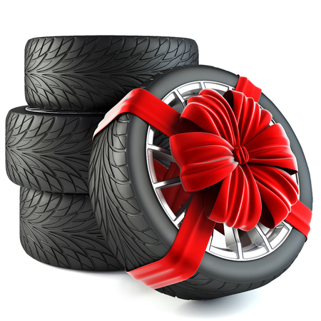 white ribbon: tires wrapped in red gift ribbon with a bow. isolated on white background.