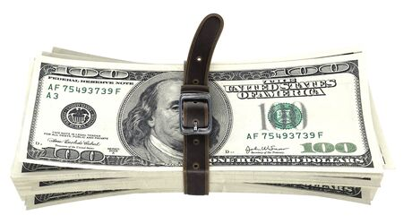 thrift: dollar bills squeezed together by leather belt. isolated on white background. Stock Photo