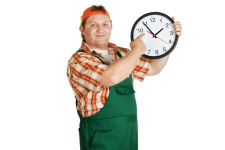 Work in a baseball cap and overall with big round clock photo