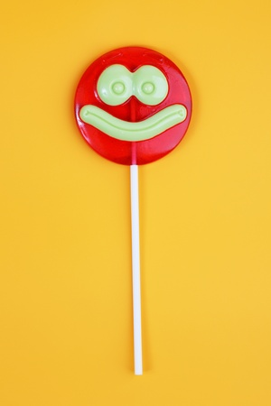 Lollipop, like a smiley face on an orange background photo