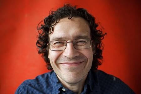 sarc�stico: Shaggy hombre sonriente con gafas y sin afeitar en un fondo anaranjado Foto de archivo
