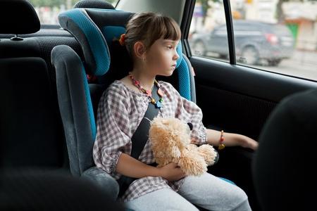 enfant banc: La petite fille dans la voiture chaise avec un ours en peluche