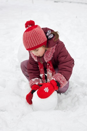 varmint: The little girl fashions snowman in winter forest Stock Photo