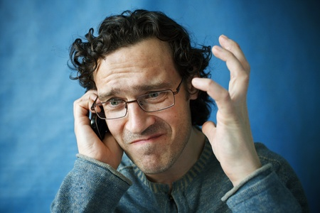 bespectacled man: The man in spectacles emotional talking on a cell phone