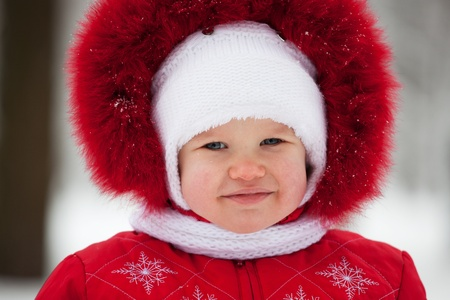 Baby in a winter suit and white cap