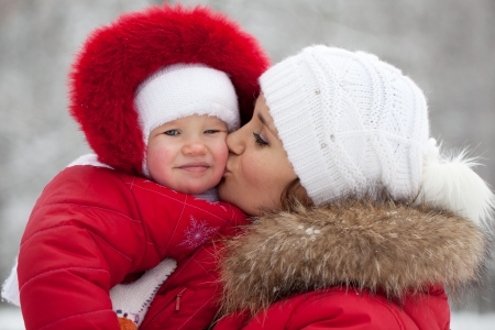 fur hood: Young mother with her baby daughter in their red jackets Stock Photo