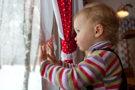 pry: The little girl stands and sees something in the window Stock Photo