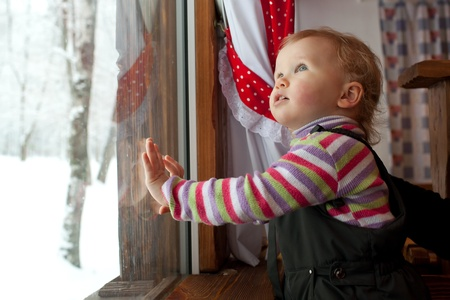 interested: The little girl is looking out the window at the cafe Stock Photo