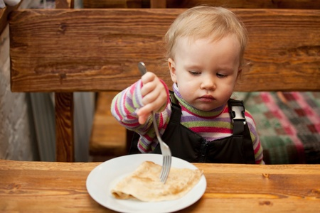 Blond little girl eats pancakes at a wooden table