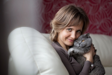 Young woman sitting on the couch and fondles gray cat