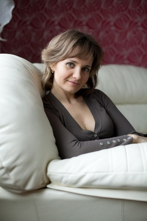 settled: Young beautiful woman, settled comfortably on a leather couch