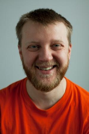 Rustic laughing good-natured man in orange t-shirt