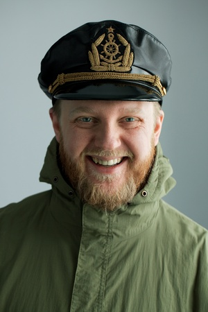 Young bearded sailor cap and green jacket photo