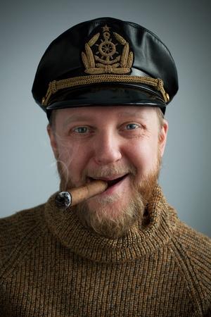 Seaman met een rokende sigaar, gebreide trui en muts Stockfoto