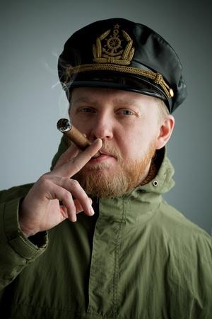 Sailor's cap and jacket smoking a cigar