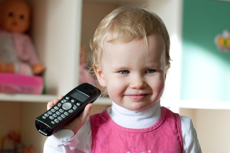 intercommunication: The little girl in a pink dress black handset