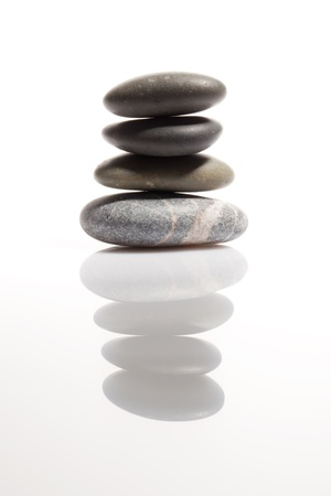 Stack of smooth stones on the mirror surface photo