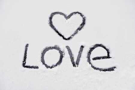 The heart and the word of love, drawn on a snow-covered glass photo