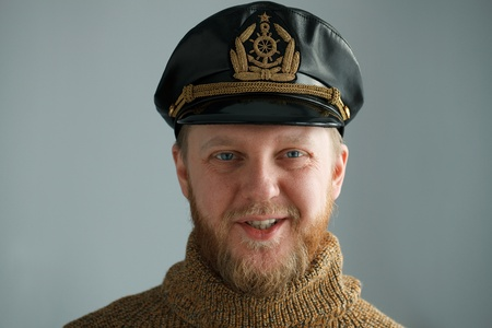 Smiling, bearded captain in a brown sweater photo