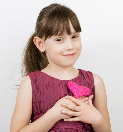 Little girl with a toy heart in his hands