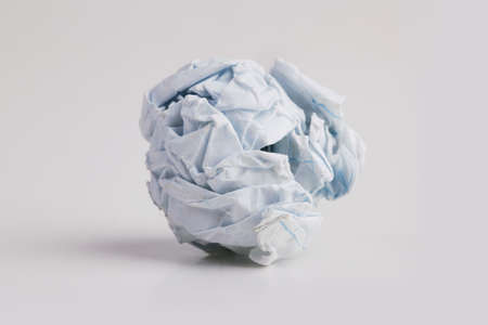Tightly crumpled piece of paper on a white background photo
