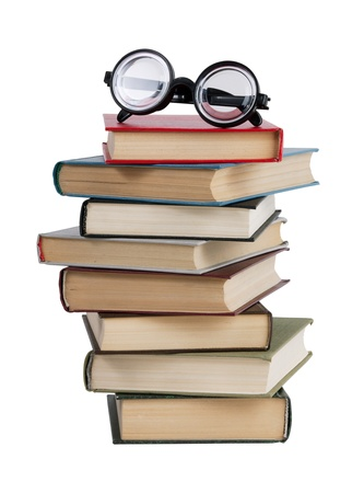 Glasses and a stack of books on white background
