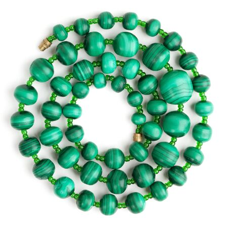 Beads made of malachite, rolled in a spiral on a white background