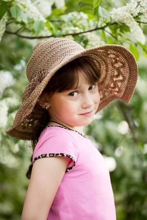 minx: Portrait of little coquette in a wicker hat