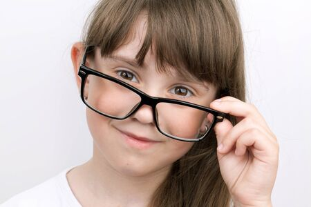 Small long-haired girl with glasses in adults Stock Photo