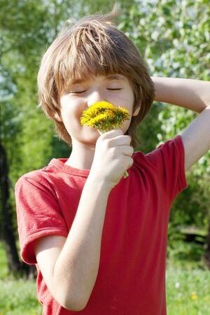beatitude: Teenager enjoys odors from dandelions on a sunny day