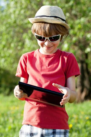 gaiety: Joyful boy plays in the Tablet PC on the nature
