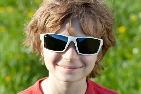 Blonde naughty little boy wearing sunglasses on a sunny day Stock Photo - 13665592