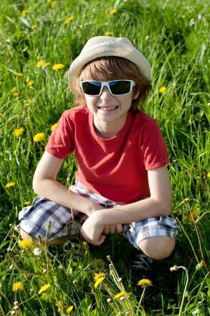 blithe: The blond boy in shorts and a panama hat of flowering dandelions Stock Photo
