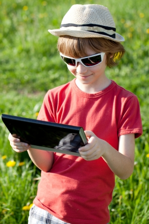 Boy playing with enthusiasm in the Tablet PC on the nature photo
