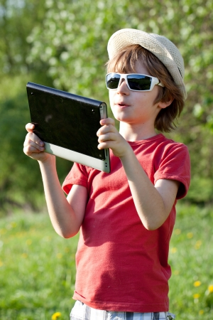 The fair-haired boy plays in the Tablet PC sunny day photo